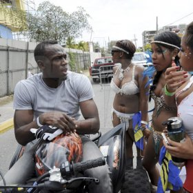 Norman Grindley/Chief Photographer Usain Bolt, riding a quad, has the attention of three beautiful young ladies during the Bacchanal Road March yesterday.     Carnival road march,  April 7, 2013.