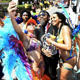 Gladstone Taylor<\n>Selfie time! Simone Mahfouz (left) and Kerah Bryant, snap a selfie with Trinidadian soca sensation Machel Montana during Xodus Carnival road march yesterday.