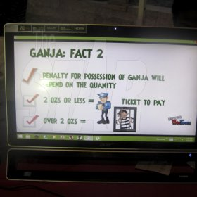 Mel Cooke<\n>Facts about Ganja displayed on a screen.