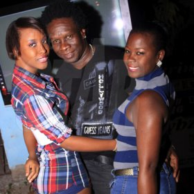Anthony Minott/Freelance Photographer DJ Flavour Wayne (centre), in company with two female friends during Pon Di Spot Fridayz, Drewsland, in St Andrew recently.